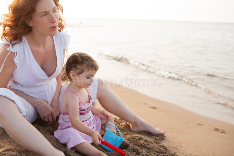 怀孕的使用在海滩沙子的母亲和女儿 免版税库存照片