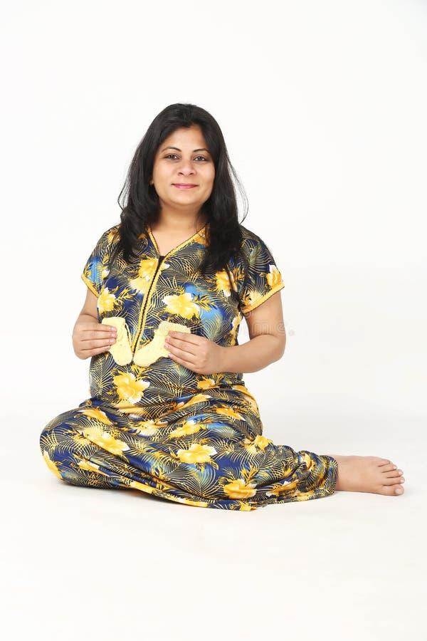 怀孕的夫人在手中拿着婴孩袜子与微笑面孔并且坐地板 图库摄影