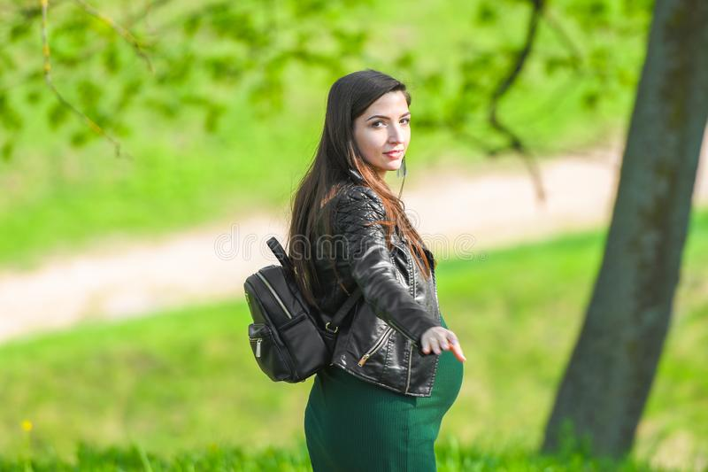 怀孕的女孩享有生活 一美丽的孕妇的画象 愉快的夫人微笑和高兴 被伸出的胳膊和 库存照片