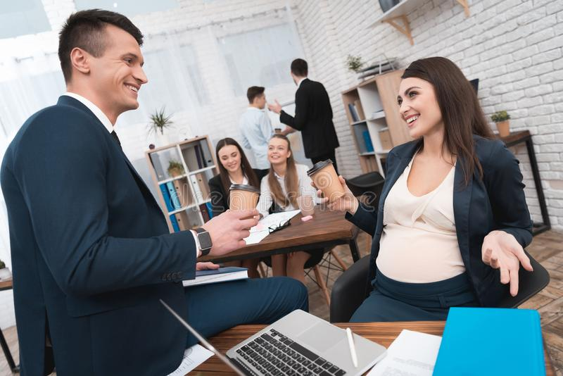 怀孕的女孩在办公室喝与院长的咖啡在办公室 怀同事 免版税库存照片