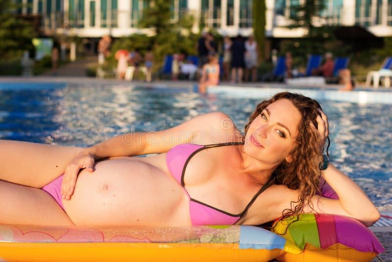 怀孕的女孩在床垫说谎在水池附近 免版税库存照片