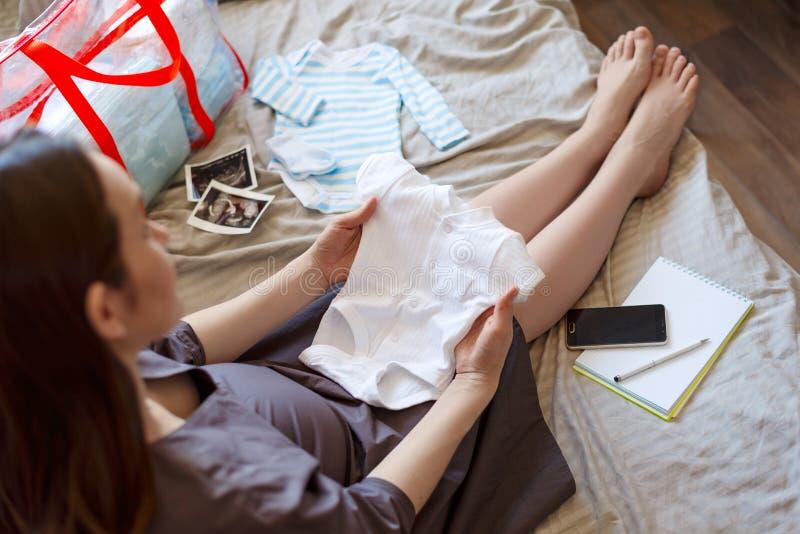 怀孕的女孩坐拿着婴孩女衬衫,在医院的费的床 免版税库存图片