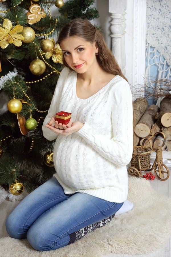 怀孕的女孩坐他的膝部和举一个蜡烛 图库摄影