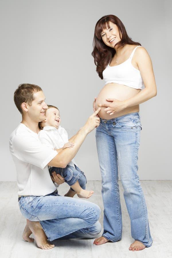 怀孕的家庭、母亲父亲孩子、愉快的父母和孩子 图库摄影