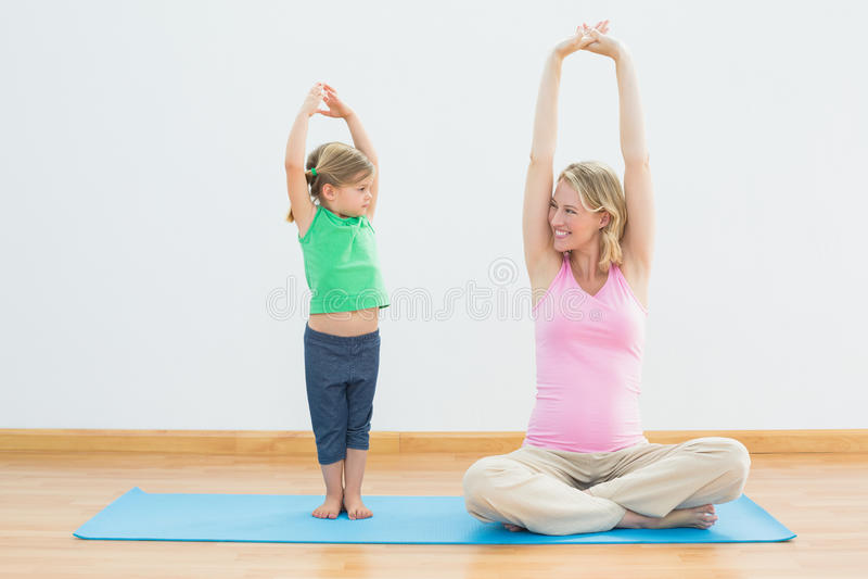 怀孕的微笑的一起做瑜伽的母亲和女儿 图库摄影