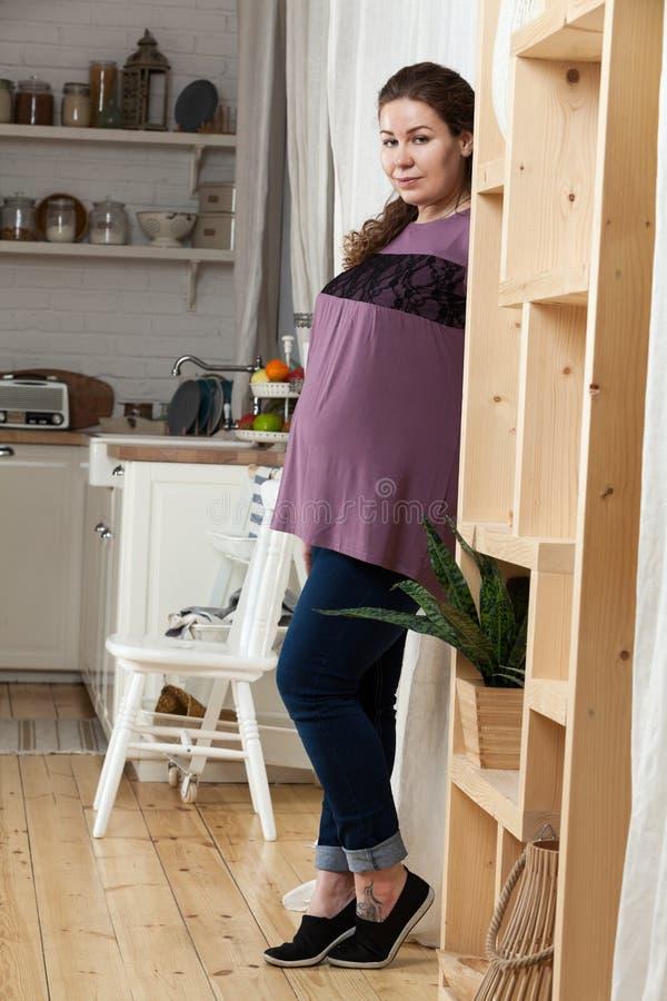 怀孕的欧洲妇女身分在厨房里,看照相机,全长画象 免版税图库摄影