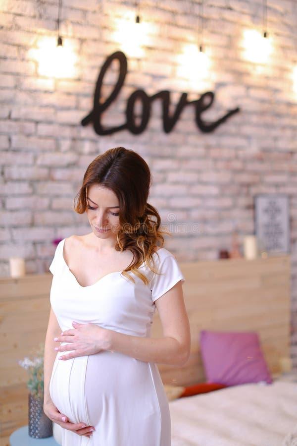 怀孕的欧洲握腹部,在砖墙上的题字爱的妇女佩带的白色礼服 库存图片