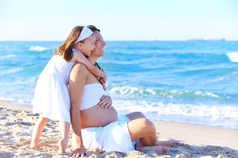 怀孕的母亲和女儿海滩的 库存照片