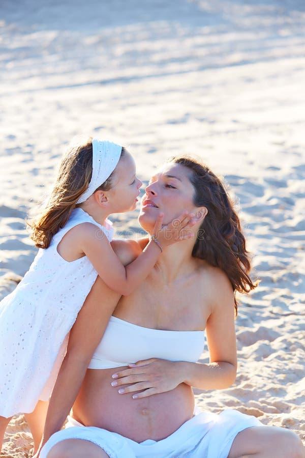 怀孕的母亲和女儿海滩的 免版税库存照片