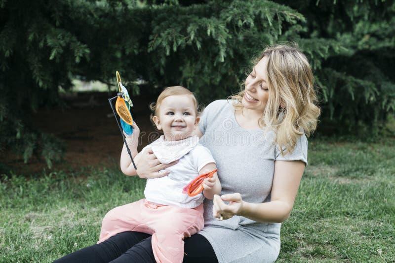 怀孕的母亲和小女孩草的 免版税库存图片