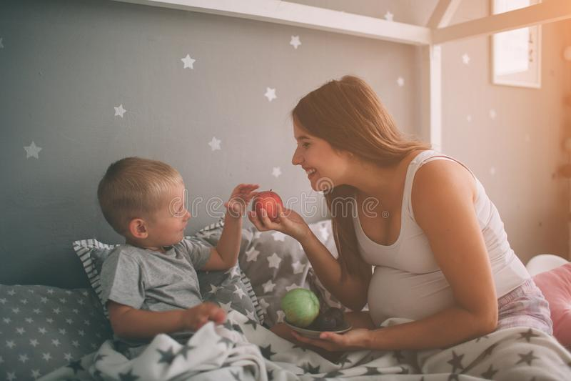 怀孕的母亲和小男孩儿子在床t家吃着一个苹果和桃子早晨 偶然生活方式 免版税图库摄影
