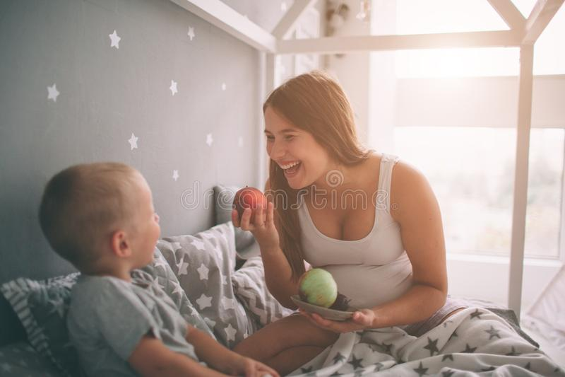 怀孕的母亲和小男孩儿子在床t家吃着一个苹果和桃子早晨 偶然生活方式 免版税库存图片