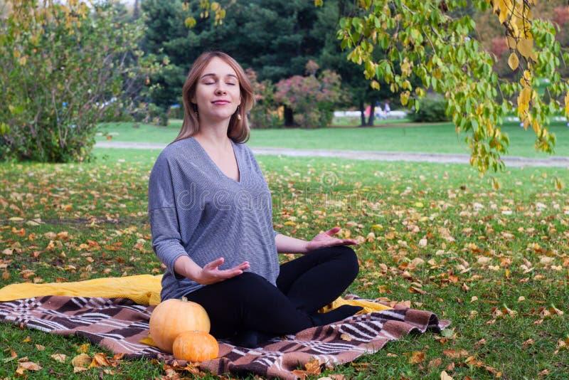 怀孕的母亲的休息 美丽的年轻孕妇坐草在做呼吸的莲花姿势的公园行使 免版税库存图片