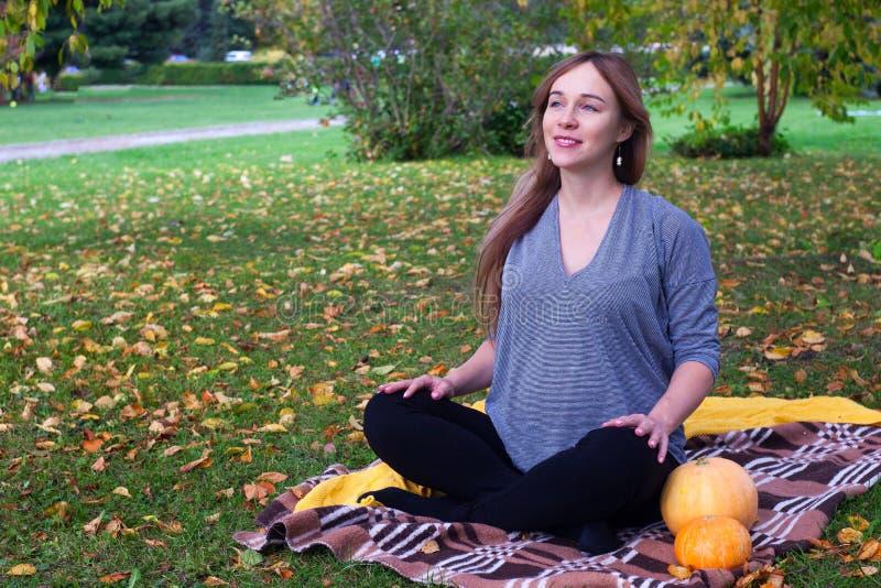 怀孕的母亲的休息 美丽的年轻孕妇坐草在做呼吸的莲花姿势的公园行使 库存图片