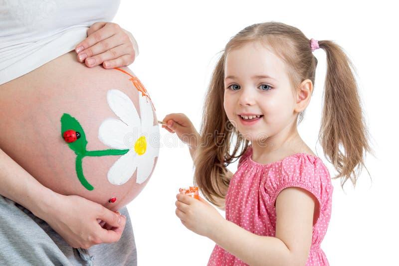 绘怀孕的母亲的腹部的小女孩 免版税库存照片