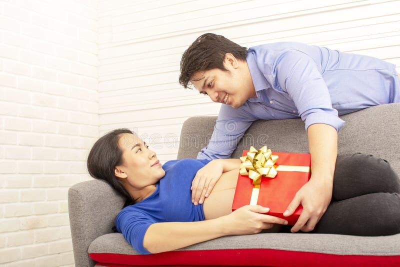 怀孕的母亲 家庭的一件礼物 在沙发的微笑的怀孕的女性开会有她未来的婴孩的礼物的 父亲和 库存图片