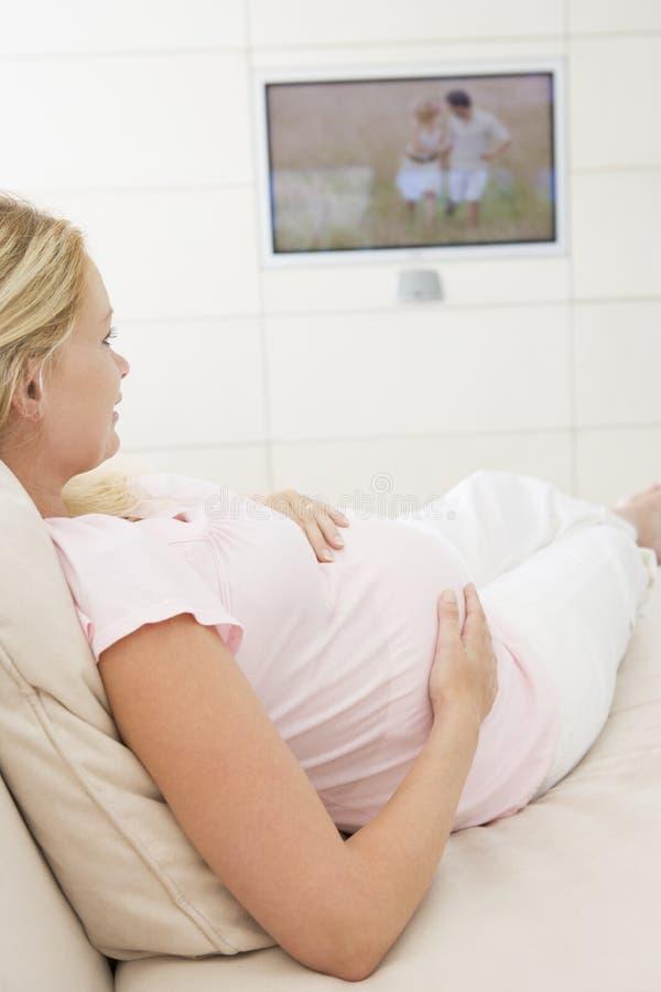 怀孕的电视注意的妇女 免版税库存图片