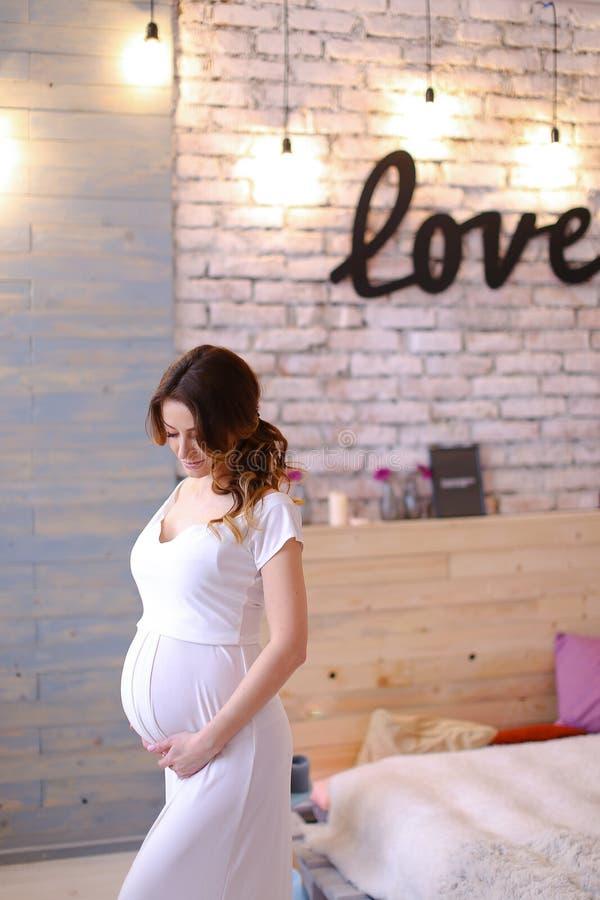 怀孕的白种人握腹部,在砖墙上的题字爱的妇女佩带的白色礼服 免版税库存照片