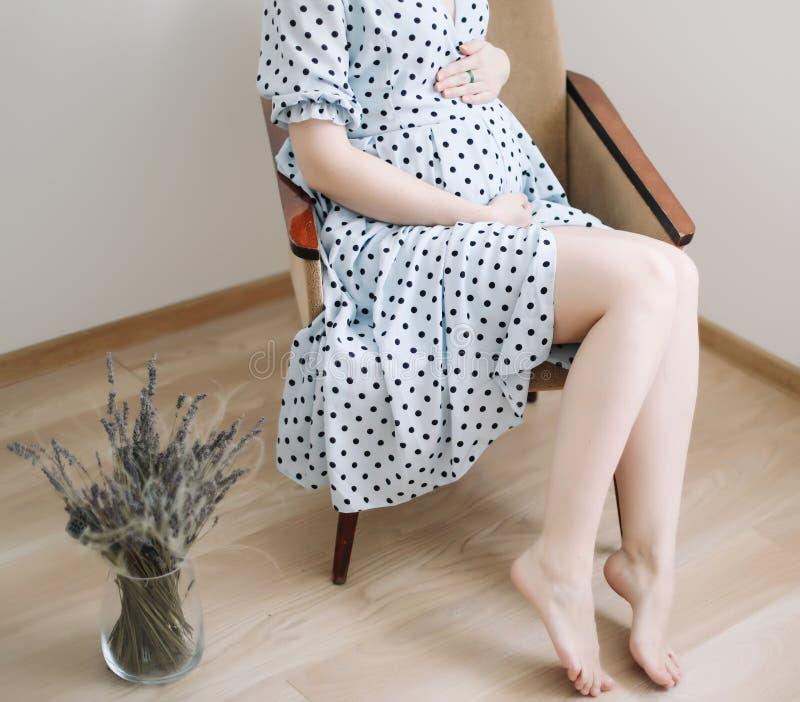 孕妇握在腹部的手 怀孕、母道、准备和期望概念 免版税库存图片