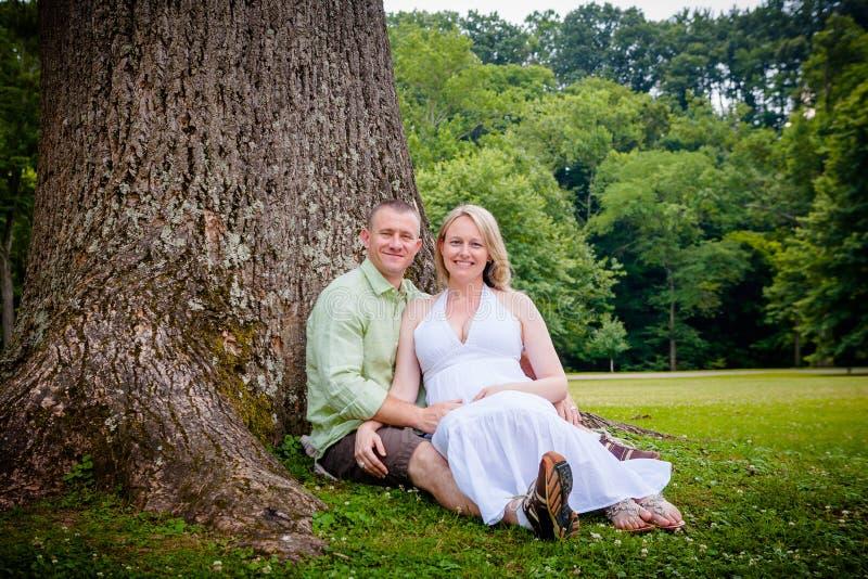 怀孕:坐外面由树的未来父母 免版税库存图片