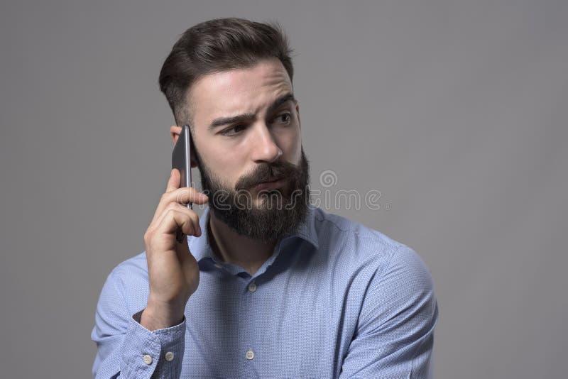 怀疑不定的有胡子的商人谈话在注视着在肩膀的手机copyspace 图库摄影