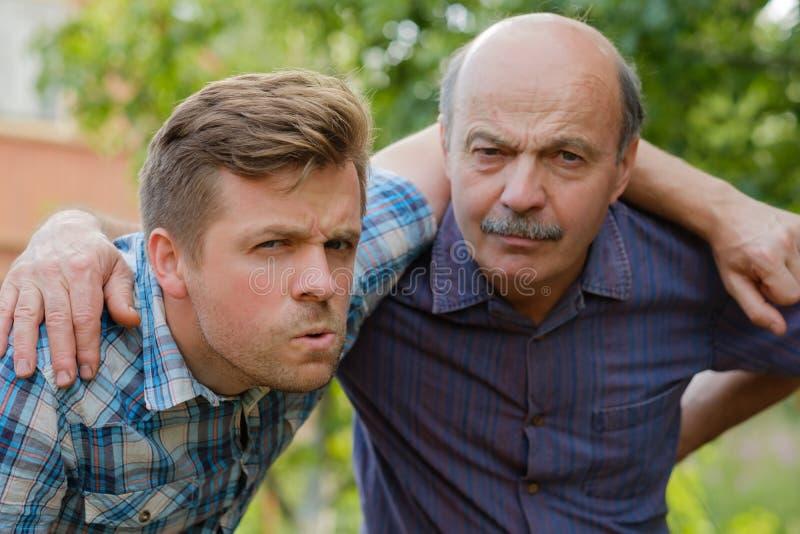 怀疑人画象  爸爸和儿子看起来向前和皱眉 免版税图库摄影