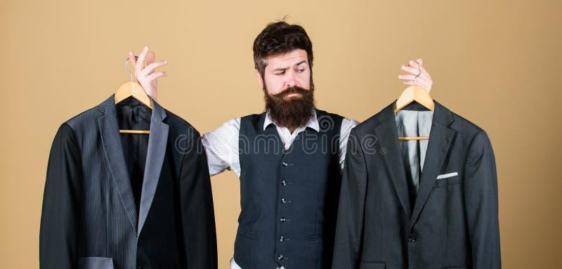 怀疑关于他的选择 有胡子的人藏品衣服夹克在商店,挑选概念 做出购物的选择的行家  免版税图库摄影