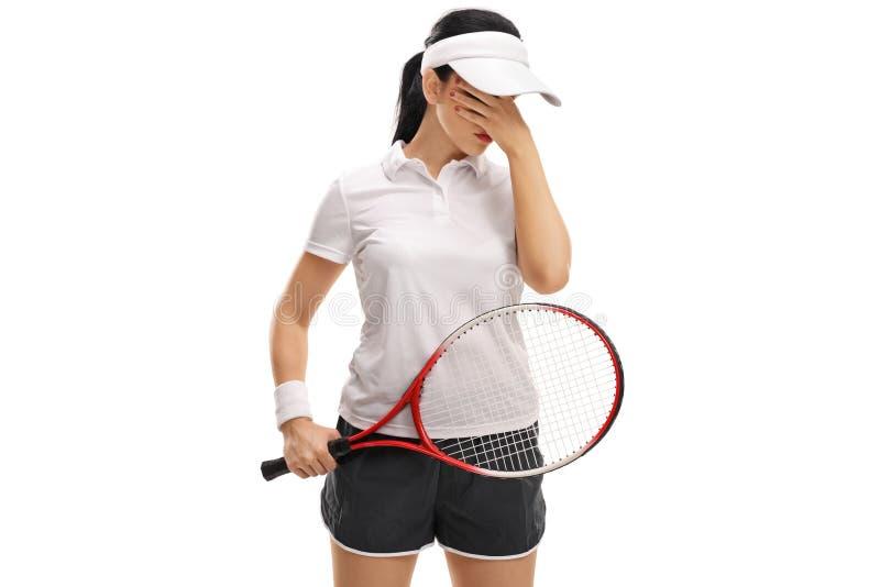怀疑地拿着她的头的女性网球员 库存照片