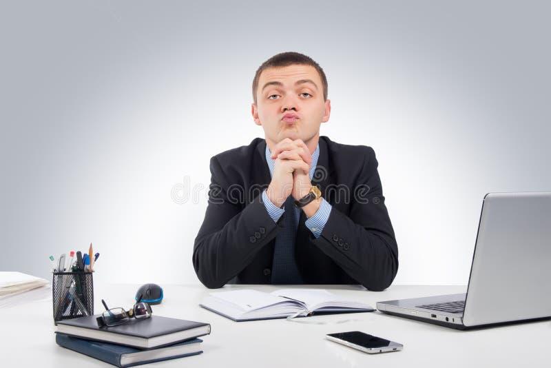 怀疑地看您的严肃的商人坐在他的de 免版税库存图片