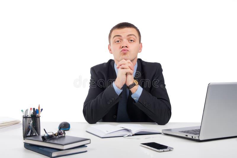怀疑地看您的商人坐在他的书桌 免版税库存图片