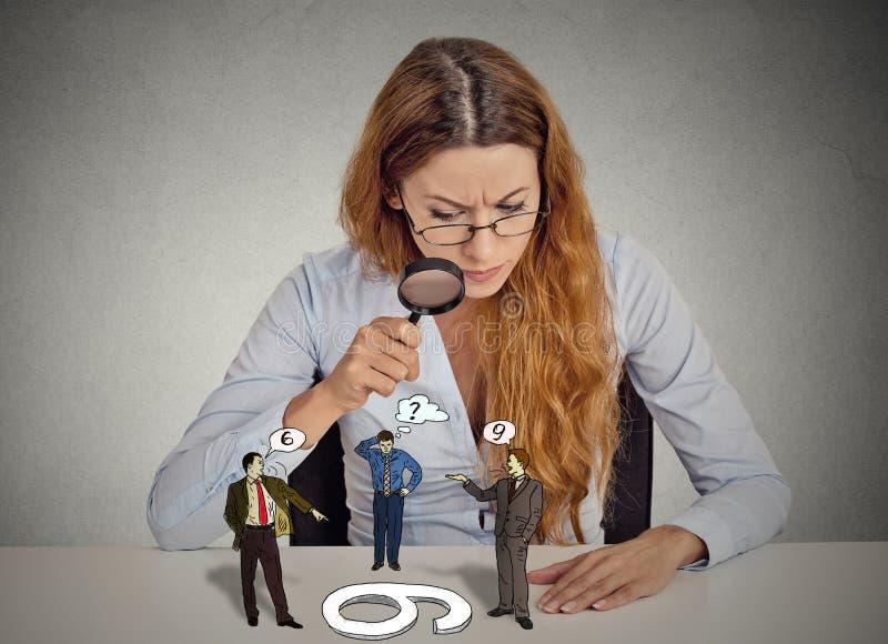 怀疑地看的女实业家争论人通过放大镜 库存照片