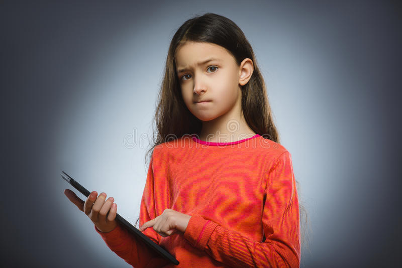 怀疑女孩或少年有片剂个人计算机计算机的 免版税库存照片