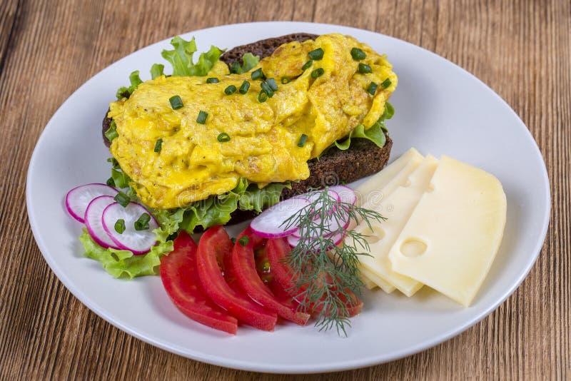怂恿在黑面包片断的煎蛋卷用红色蕃茄、乳酪和萝卜在一张木桌上,关闭 图库摄影