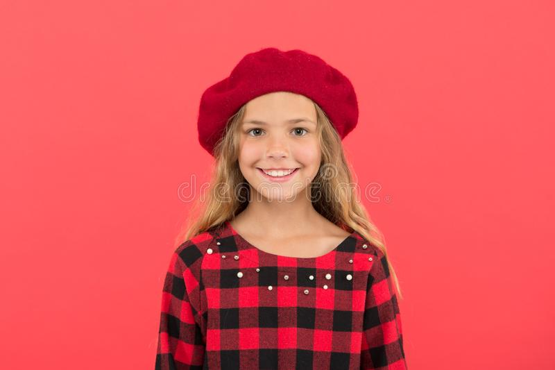 怎么穿象时尚女孩的贝雷帽 有摆在帽子和方格的礼服的长发的孩子女孩在红色背景 库存照片