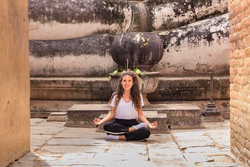 思考在佛教寺庙的瑜伽位置的女孩 免版税库存照片