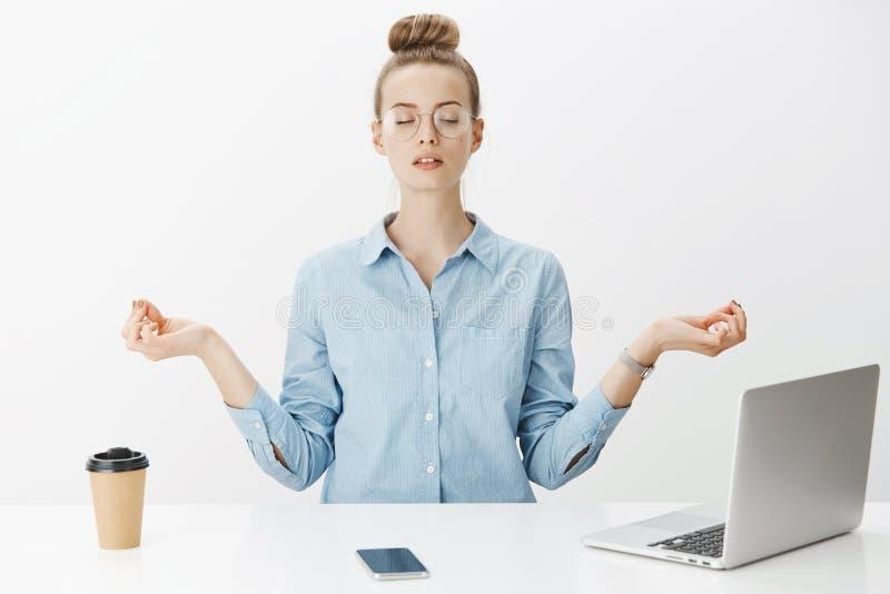 思考在工作的女孩坐在与涅磐天体的莲花姿势在膝上型计算机和智能手机尝试附近放松并且摆脱 免版税库存图片