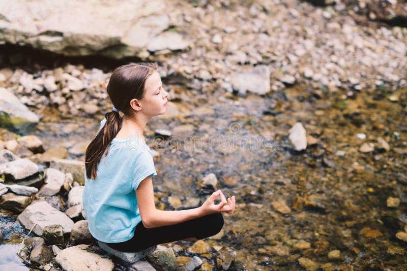 思考在日出的少女瑜伽在山小河的岸 免版税图库摄影