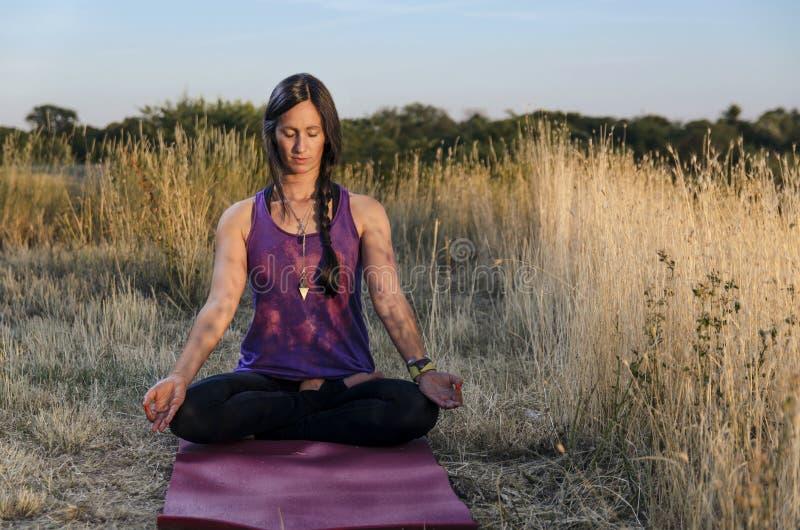 思考在有眼睛特写镜头的瑜伽席子的女孩 库存照片