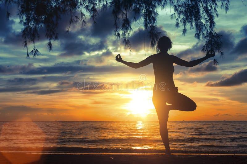 思考在海海滩的女孩在美妙的日落期间 瑜伽和健身 库存图片
