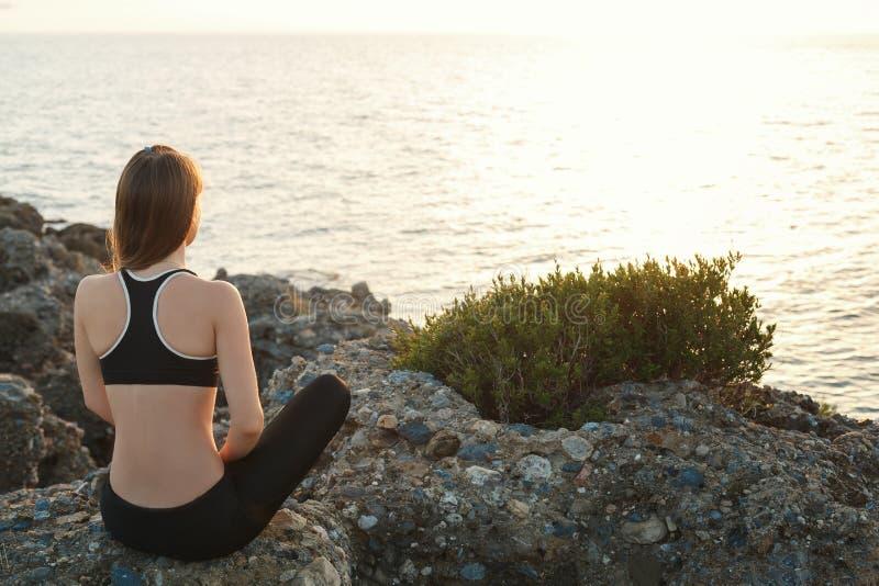思考在海滩的女孩在日落 免版税库存照片