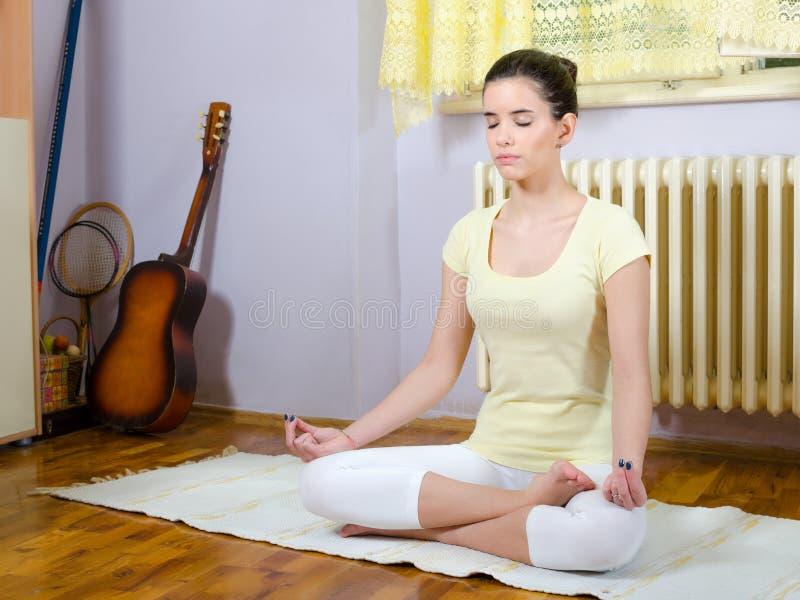 思考在瑜伽姿势的十几岁的女孩在她的屋子里 图库摄影