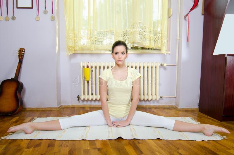 思考在瑜伽姿势的美丽的十几岁的女孩在屋子里 库存照片
