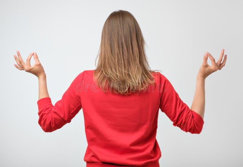 思考在红色衬衣的镇静美丽的白种人妇女室内画象,微笑,当举有禅宗的时手打手势 免版税库存图片
