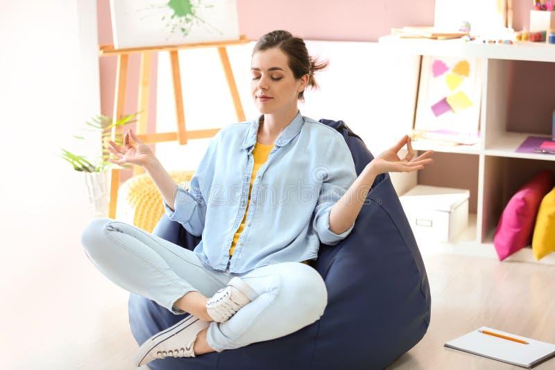 思考在装豆子小布袋椅子的年轻女性画家在演播室 免版税库存图片