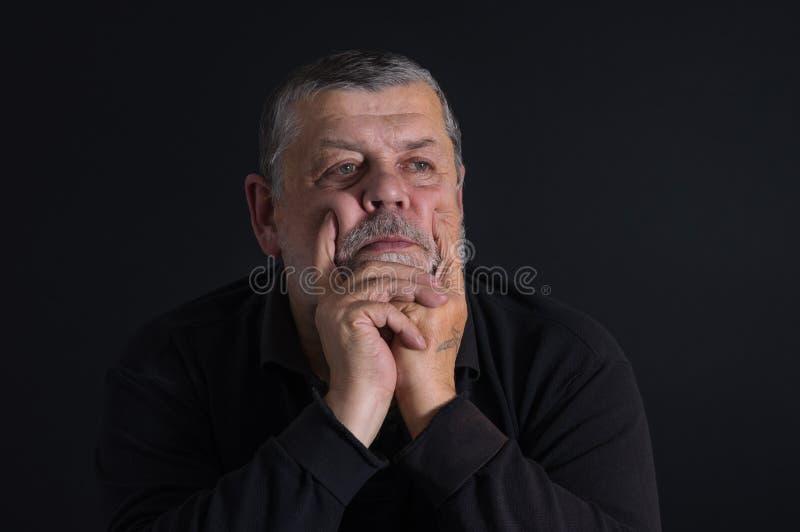 思考在黑暗中的有胡子的白种人老人画象  免版税库存照片