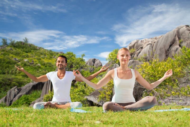 思考愉快的夫妇做瑜伽和户外 库存图片