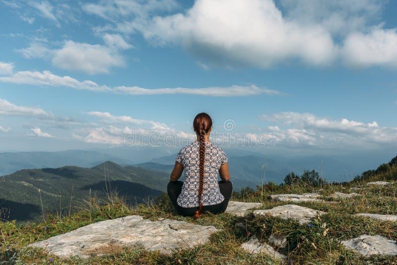 思考或做瑜伽的少妇,当坐与不可思议的山风景时的岩石上面 免版税库存照片