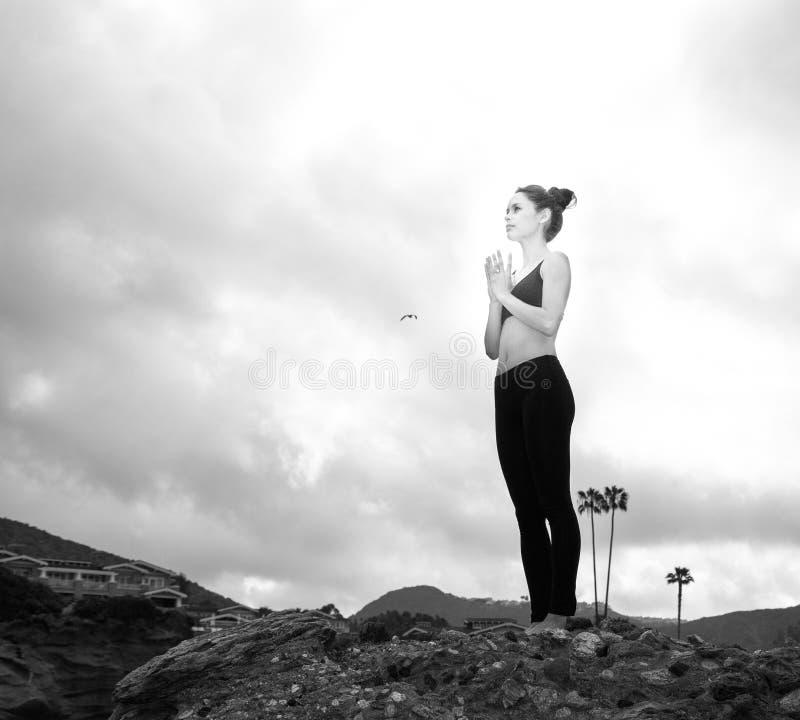 思考美丽的妇女站立在岩石顶部和 免版税库存图片