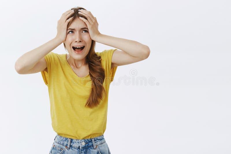 急切和困厄的妇女恐慌的感觉握在头的手从恐慌叫喊混乱和关心,皱眉 免版税库存图片