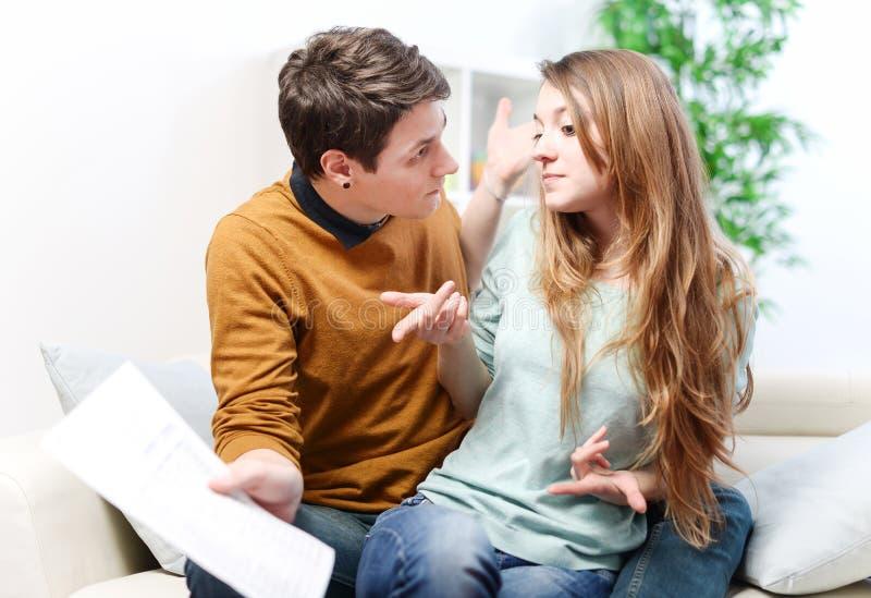 年轻急切夫妇通过咨询他们的银行帐户争吵 库存图片